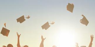 graduates throwing caps into air in sunset